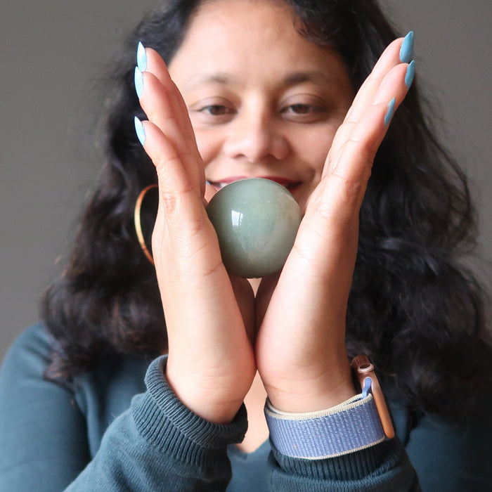 sheila of satin crystals holding a green aventurine crystal ball in between hands