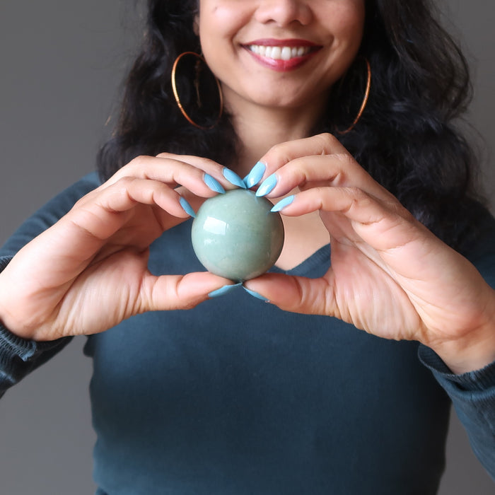 holding a green aventurine crystal ball