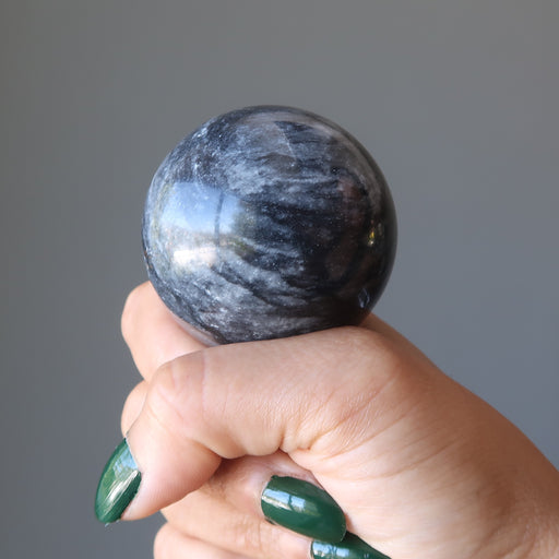 gray and white aventurine sphere on hand