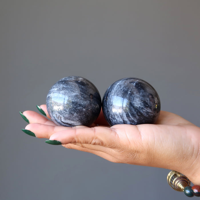 hand holding 2 gray and white aventurine spheres