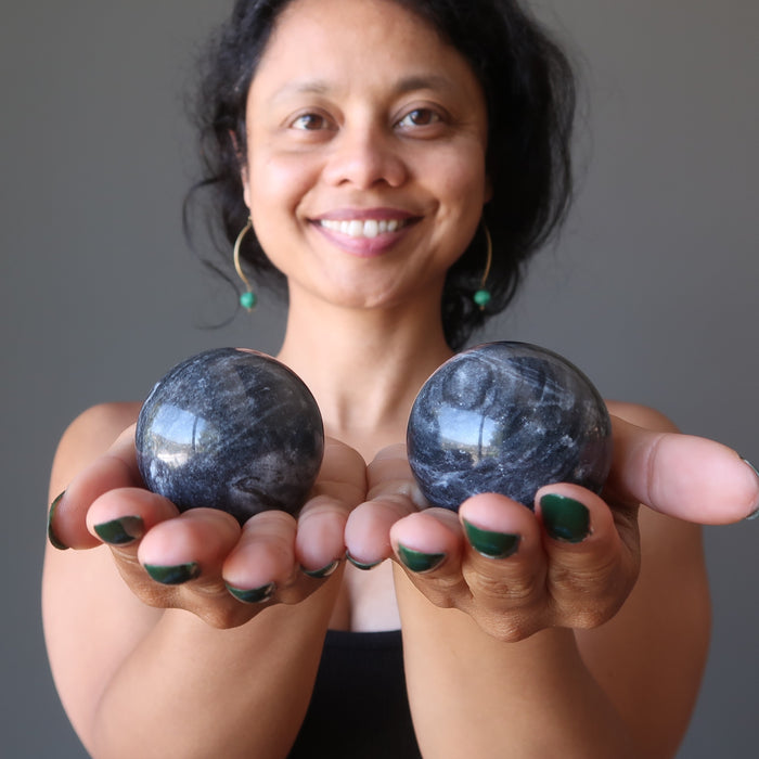 sheila of satin crystals holding gray and white aventurine spheres in her palms