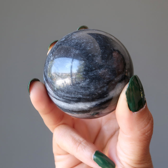 hand holding gray and white aventurine sphere