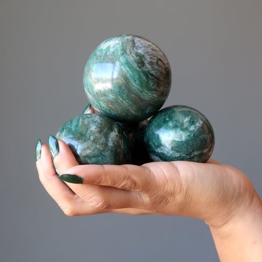 hand holding a pile of green and white streaked aventurine spheres