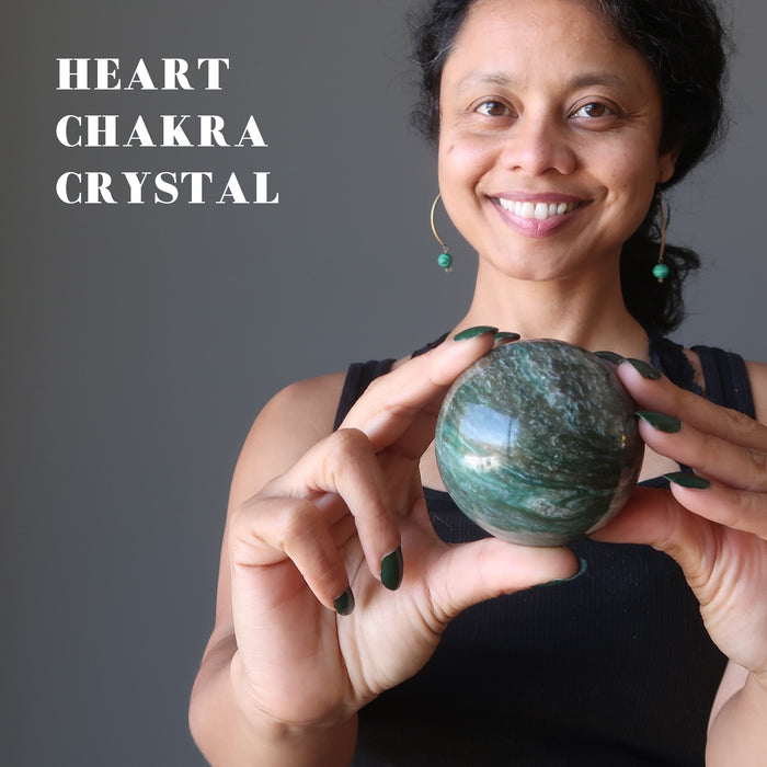 sheila of satin crystals holding green and white streaked aventurine sphere in front of her heart chakra