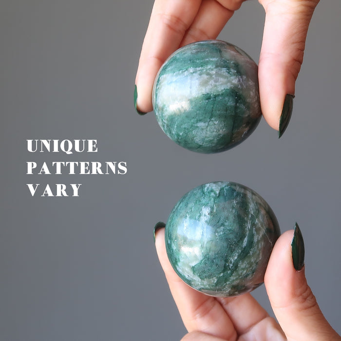 hands holding green and white streaked aventurine spheres to show unique patterns vary in each
