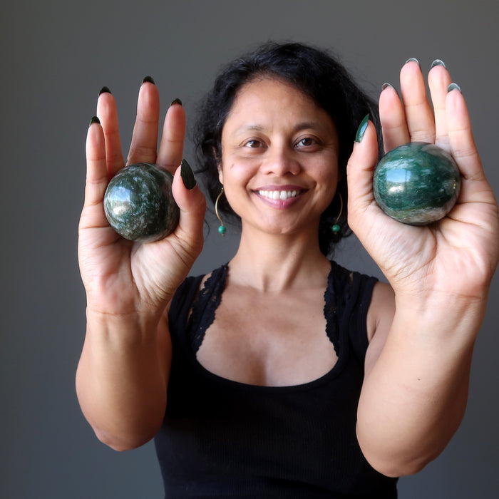 sheila of satin crystals holding green and white streaked aventurine spheres in her palms