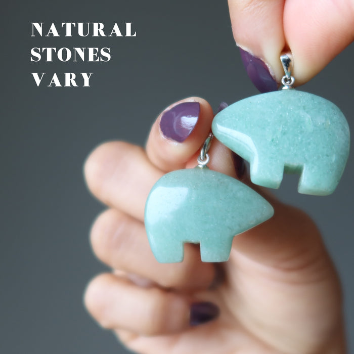 hand holding aventurine bear pendants to show natural stones vary