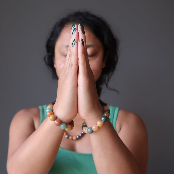 sheila of satin crystals with hands in prayer wearing multi colored aventurine stretch bracelets