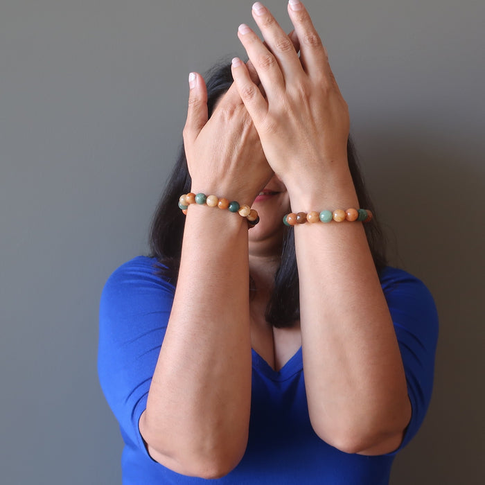 jaren of satin crystals with hands in front of her face wearing multi colored aventurine stretch bracelets