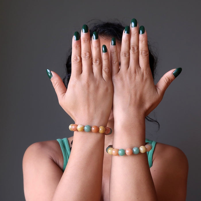sheila of satin crystals wearing multi colored aventurine stretch bracelets with hands in front of her face