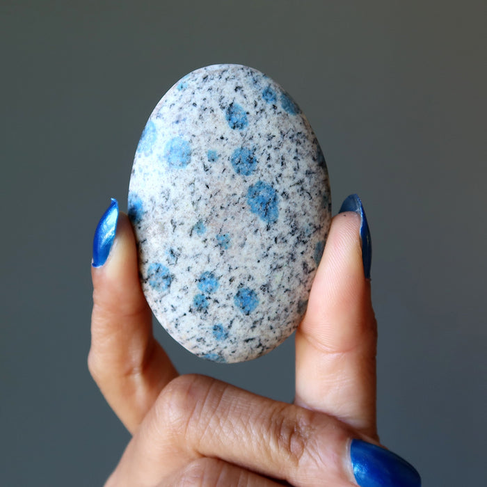 hand holding blue azurite in granite polished oval palm stone