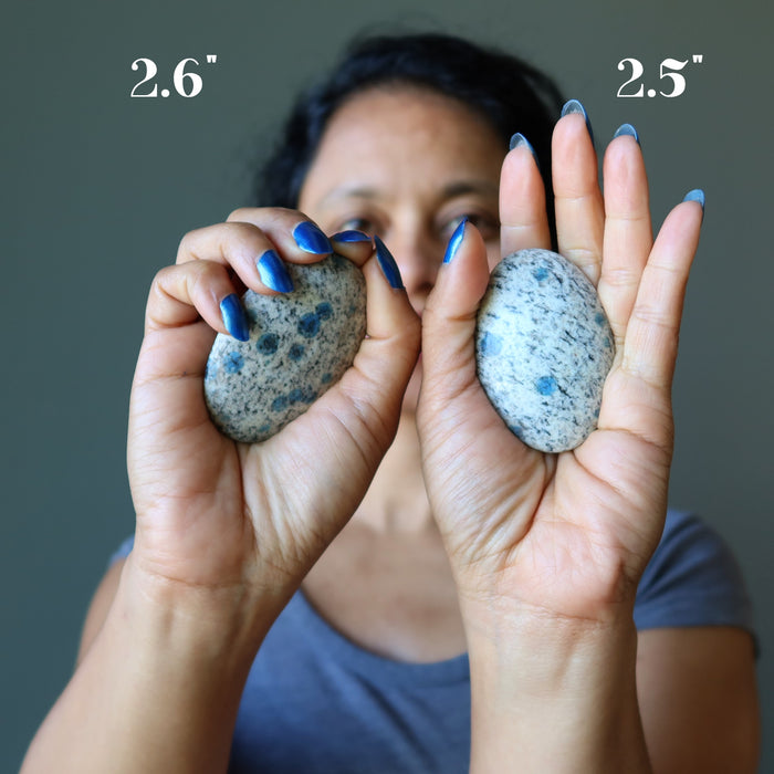 sheila of satin crystals holding two azurite palm stones in her hands to show size difference