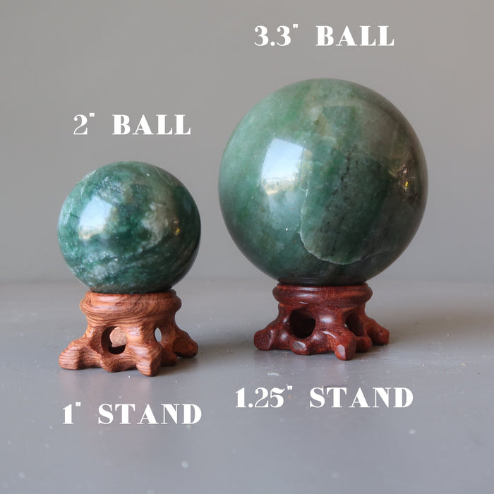 two green aventurine spheres on brown pedestal display stands in varying sizes
