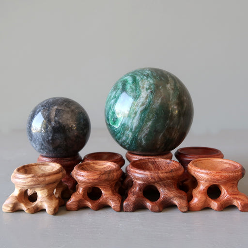 one gray and one green aventurine sphere on fancy crystal ball display stands in varying shades of brown wood