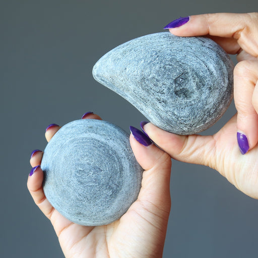hands holding a pair of basalt stone