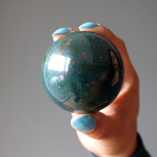 hand holding an indian bloodstone sphere