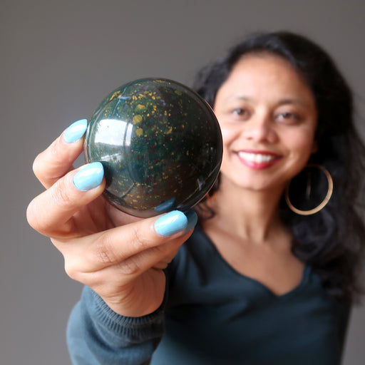sheila of satin crystals holding a bloodstone crystal sphere