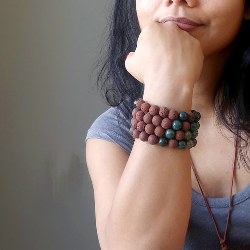 female hand on chin wearing 4 red lava and indian bloodstone round beaded stretch bracelets