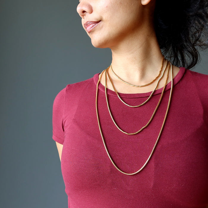 female model of satin crystals wearing 4 gold plated brass snake chain necklaces to show the different lengths