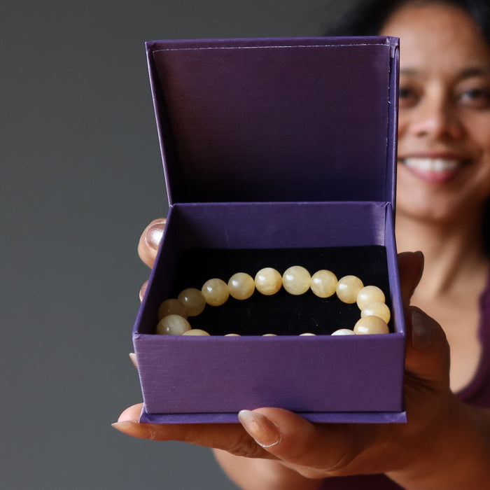 sheila holding a satin crystals gift box with a yellow calcite beaded stretch bracelet