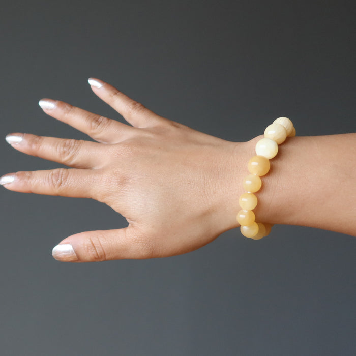 hand wearing a yellow calcite beaded stretch bracelet