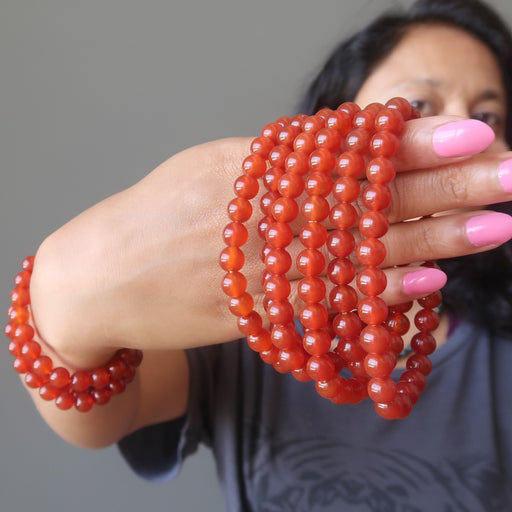sheila of satin crystals holding a stack of carnelian bracelets