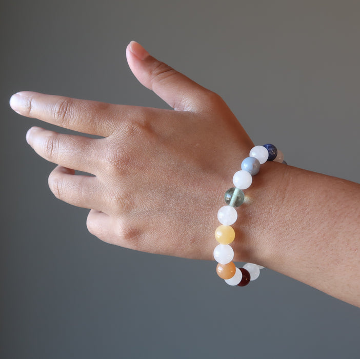 hand wearing snow white quartz chakra bracelets