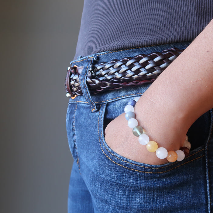 hand in jeans pocket wearing snow white quartz chakra bracelets