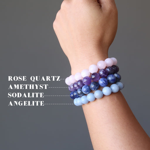 hand wearing upper chakra bracelet set including purple amethyst, blue sodalite, light blue angelite, pink rose quartz