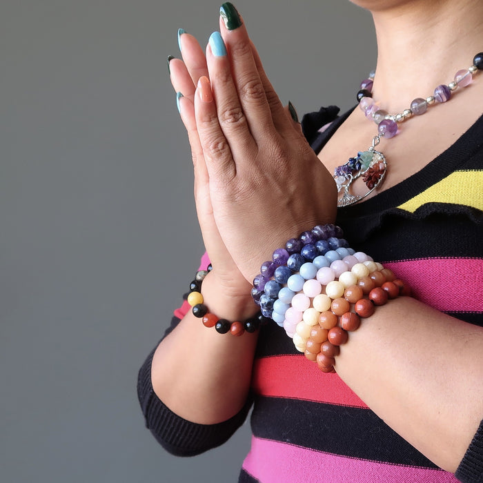 sheila of satin crystals wearing set of 7 chakra bracelets with amethyst, sodalite, angelite, rose quartz, calcite, aventurine and red jasper