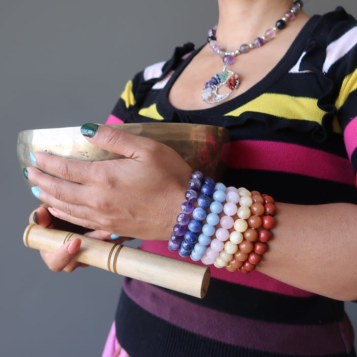 sheila of satin crystals wearing set of 7 chakra bracelets with amethyst, sodalite, angelite, rose quartz, calcite, aventurine and red jasper holding a tibetan singing bowl