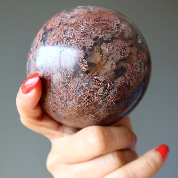hand holding up chalcedony jasper crystal ball