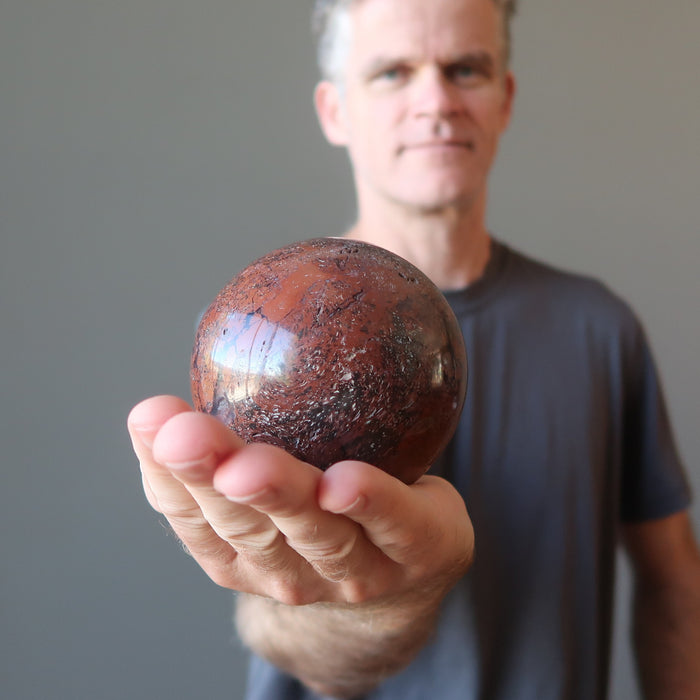 male model holding red chalcedony sphere in his hand