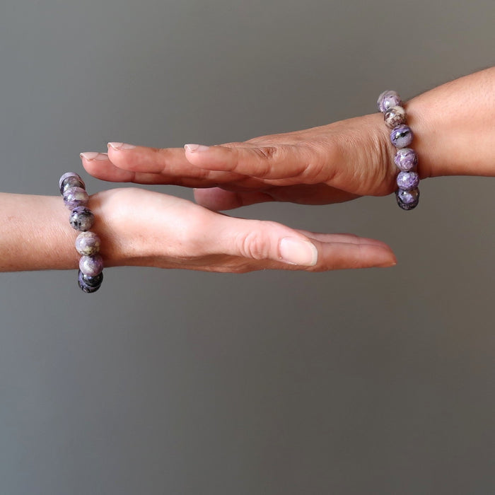 two female hands modeling purple charoite stretch bracelets