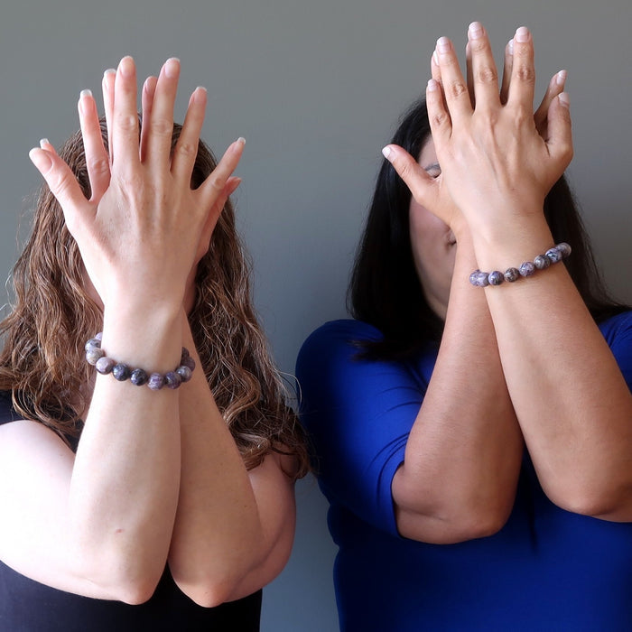 two female models with hands up in front of their faces both wearing charoite bracelets