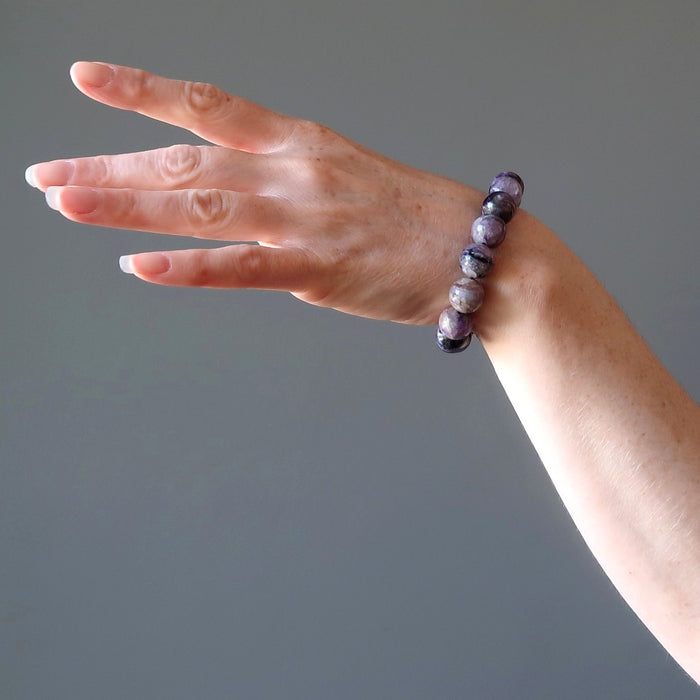 female hand modeling purple charoite stretch bracelet