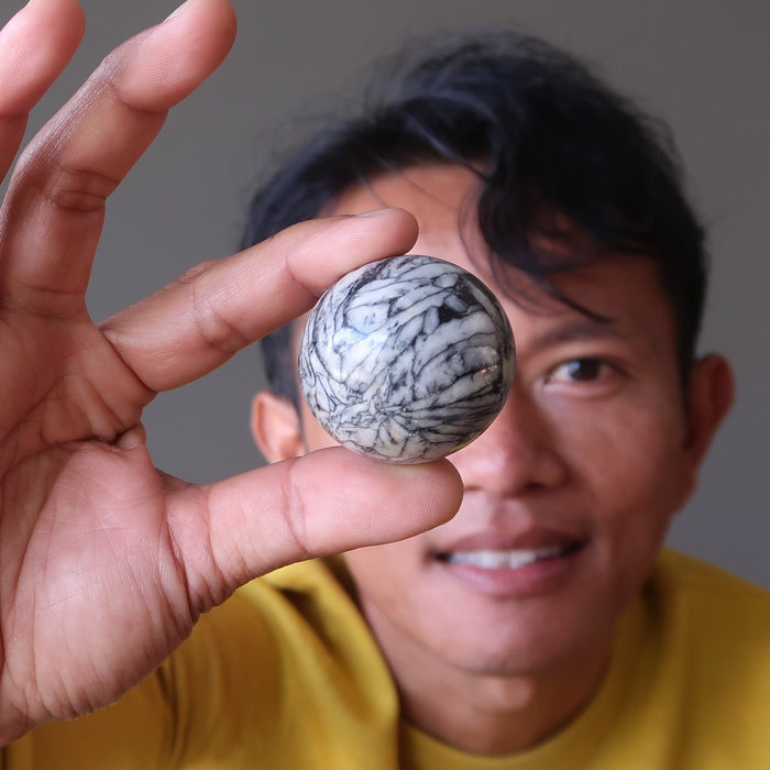 tim of satin crystals holding up a chrysanthemum stone ball in front of his eye