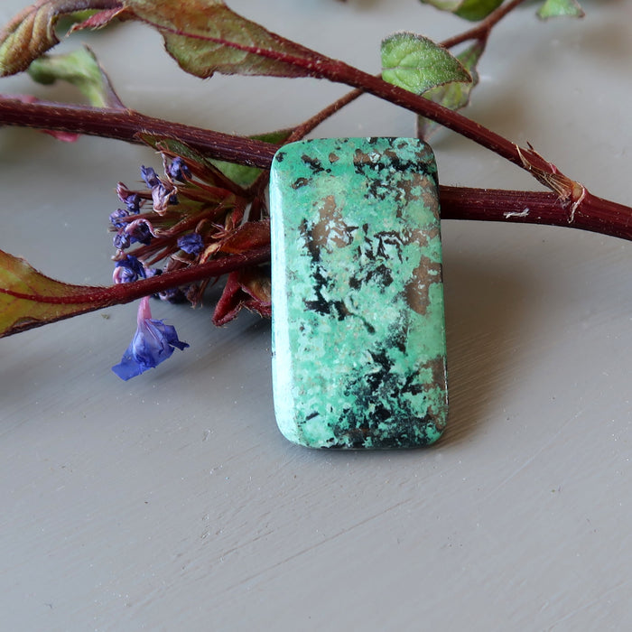 rectangular chrysocolla cabochon leaning against blue flowers