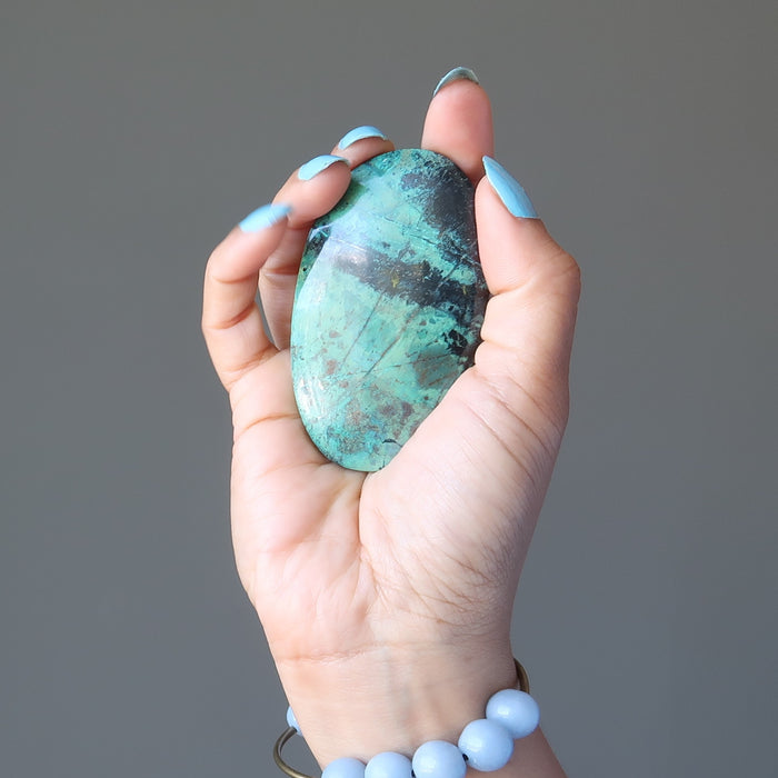 hand holding blue-green and black chrysocolla oval cabochon