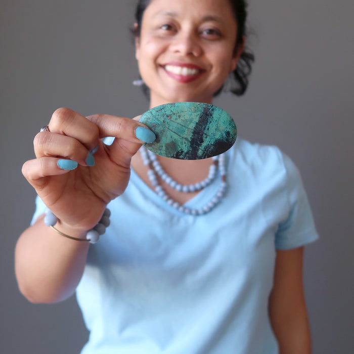 sheila of satin crystals holding blue-green and black chrysocolla oval cabochon