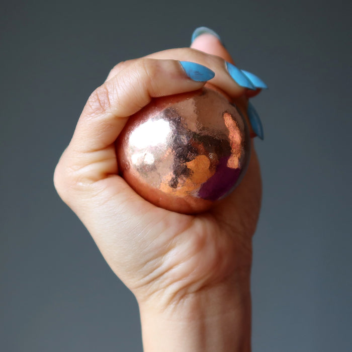 hand holding a copper alchemist sphere