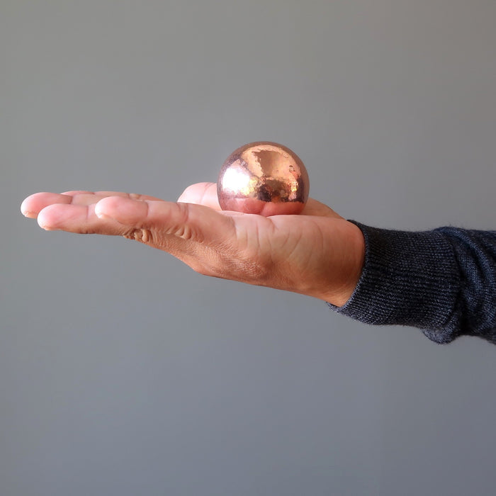 hand holding a copper sphere