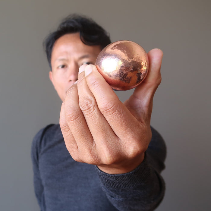 tim of satin crystals holding a copper alchemist sphere