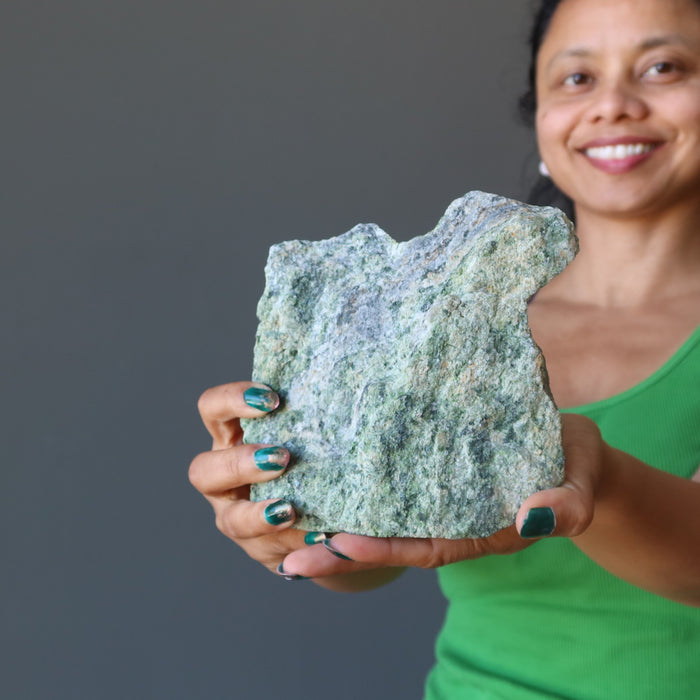 sheila of satin crystals holding rough green epidote standing mineral stone