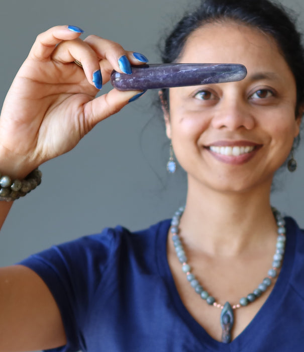 sheila of satin crystals holding a purple fluorite to her third eye chakra