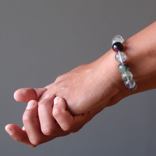 man's hand wearing rainbow fluorite beaded stretch bracelet