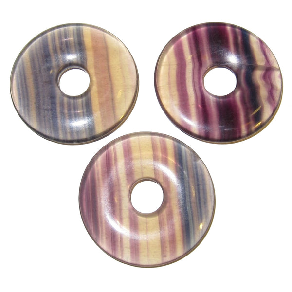 Set of three rainbow Fluorite round donut amulets that are fully polished. They are clear opaque with purple, green, and yellow stripes. Each has a hole in the center for wearing as pendant or using as is.
