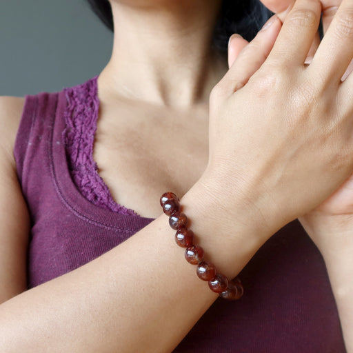 hand wearing hessonite garnet round beaded stretch bracelet