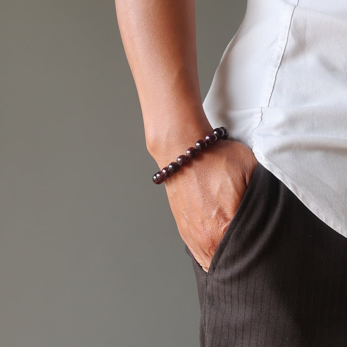 man with hand in pocket wearing red garnet bracelet