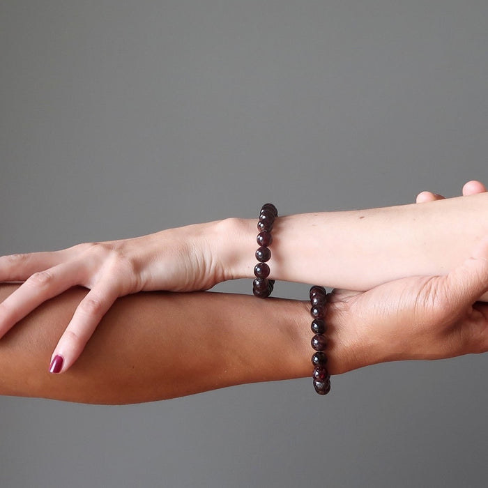 man and woman's arms wearing red garnet bracelets
